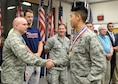First Lt. Brian Hwang, a contracting manager for the Battle Management Air Operations Center program, is welcomed home by Col. David R. Dunklee, installation commander, during the Hanscom Heroes Homecoming medallion ceremony at the base conference center July 21. During the event, base personnel formally welcomed home military and civilian Airmen, along with their families, who have returned home from deployment in the past year. (U.S. Air Force photo by Linda LaBonte Britt)