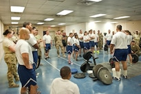 Airmen and Air Force civilians receive a briefing before participating in the deadlift portion of a powerlifting competition at Bagram Airfield, Afghanistan, July 15, 2016. The airmen are assigned to the 455th Expeditionary Aircraft Maintenance Squadron. Air Force photo by Capt. Korey Fratini