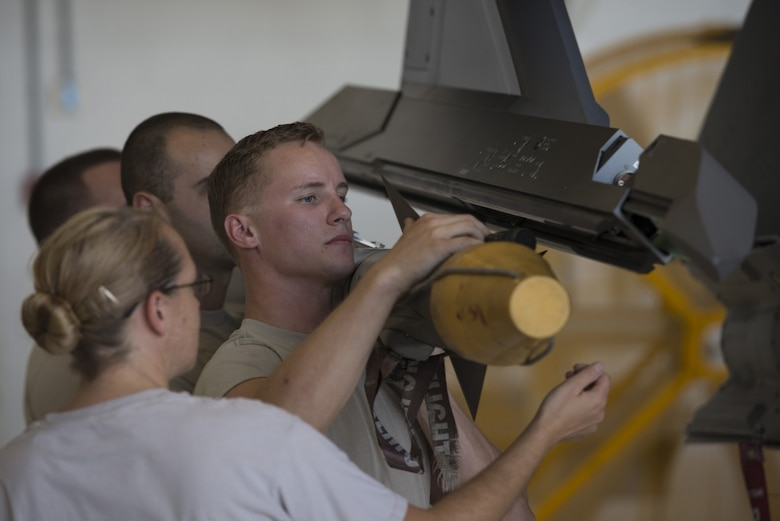 Airmen from the 33th Aircraft Maintenance Squadron load an AIM-9X missile on to an F-35A's external weapons pylon July 20, 2016, at Eglin Air Force Base, Fla. This milestone was the first time an F-35A at Eglin AFB was loaded with internal and external weapons and will help develop weapons loading procedures for the F-35 program. (U.S. Air Force photo by Senior Airman Stormy Archer)