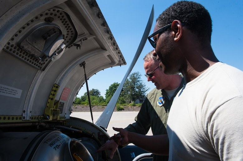 """Brig. Gen. Jon T. Thomas, 86th Airlift Wing commander, inspects the engine of a C-130J Super Hercules alongside Staff Sgt. Dominiq Saxon, 86th Aircraft Maintenance Squadron aircraft hydraulics systems journeyman, during his """"fini flight"""" July 20, 2016, at Ramstein Air Base, Germany. Thomas helped Saxon as he repaired the hydraulics system of the plane after it malfunctioned prior to takeoff. (U.S. Air Force photo/Airman 1st Class Lane T. Plummer)"""