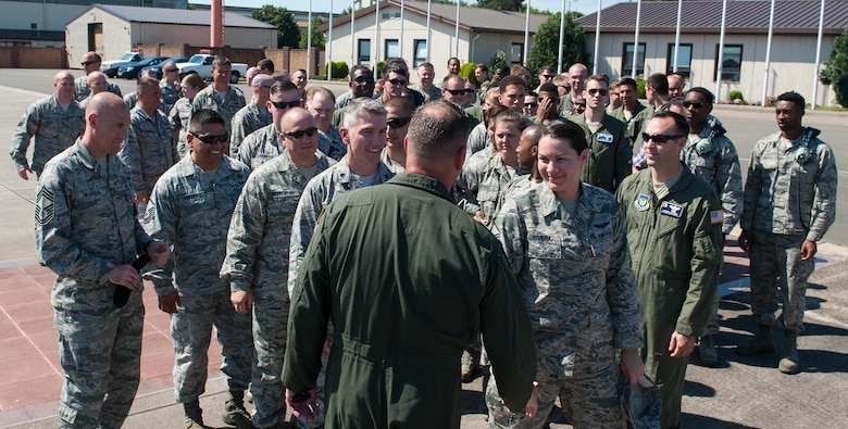 """Airmen approach Brig. Gen. Jon T. Thomas, 86th Airlift Wing commander, after his """"fini flight"""" July 21, 2016, at Ramstein Air Base, Germany. Airmen traditionally come out to greet their commanders after their final flight. (U.S. Air Force photo/Airman 1st Class Lane T. Plummer)"""