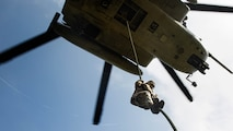A Marine student with the Fast Rope Masters Course, ran by Expeditionary Operations Training Group fast ropes out of a CH-53E Super Stallion helicopter during elevator operations at Landing Zone Kingfisher, Marine Corps Base Camp Lejeune, N.C., July 13, 2016. The new course is a shortened version of the helicopter rope suspension training course and focuses on qualifying Marines as subject matter experts within their subordinate command.