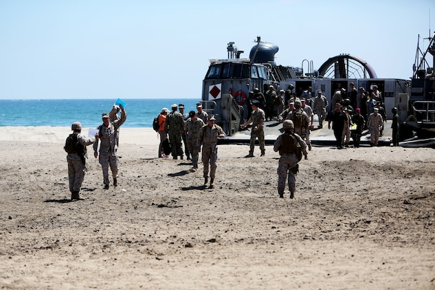 U.S. Marines with Landing Support Company, 1st Transportation Support Battalion, 1st Marine Logistics Group guide distinguished visitors off of a landing craft, air cushion during PACOM Amphibious Leaders Symposium – 16 aboard Camp Pendleton, Calif., July 13, 2016. Several 1st MLG units and Beachmaster Unit 1, Naval Beach Group 1 facilitated the offload of equipment and personnel during the symposium's beach landing operations demonstration. (U.S. Marine Corps photo by Sgt. Carson Gramley/released)