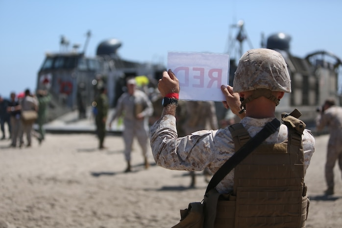 U.S. Marines with Landing Support Company, 1st Transportation Support Battalion, 1st Marine Logistics Group, guide distinguished visitors off of a landing craft, air cushion during PACOM Amphibious Leaders Symposium – 16 aboard Camp Pendleton, Calif., July 13, 2016. Several 1st MLG units and Beachmaster Unit 1, Naval Beach Group 1 facilitated the offload of equipment and personnel during the symposium's beach landing operations demonstration. (U.S. Marine Corps photo by Sgt. Carson Gramley/released)
