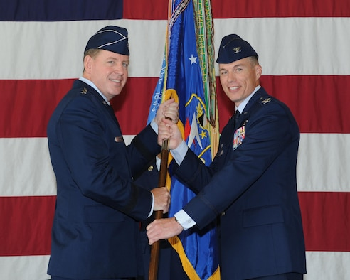 Maj. Gen. James Hecker, 19th Air Force Commander, Joint Base San Antonio–Randolph, Texas, passes the 14th Flying Training Wing guidon to Col. Douglas Gosney, the new 14th FTW Commander, during a change of command ceremony July 22 in the McAllister Fire Station at Columbus Air Force Base, Mississippi. (U.S. Air Force photo/Elizabeth Owens)