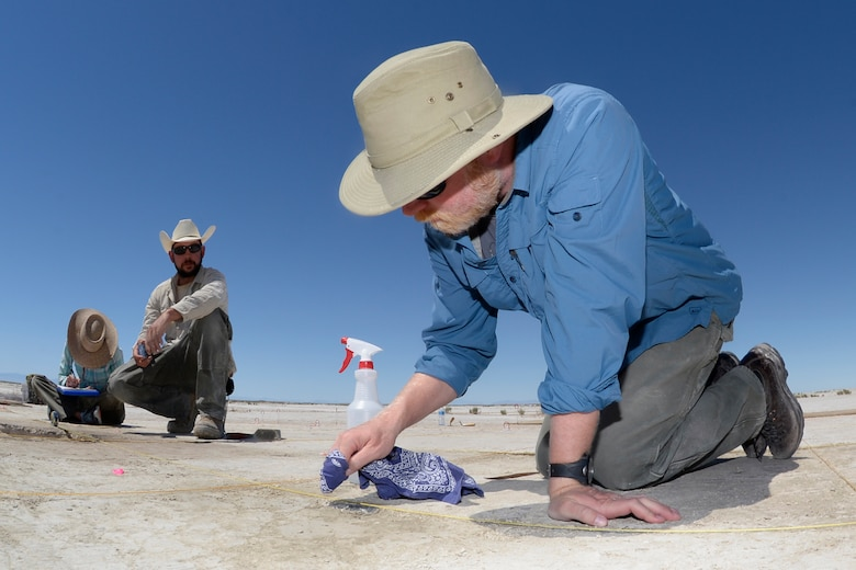 Daron Duke, Far Western Anthropological Research Group project leader, carefully cleans a large spear tip before removing it from the ground at an archaeological dig site on the Utah Test and Training Range, July 13, 2016. The spear tip was one of the principle artifacts found at the site last week, and archaeologists working there believe early humans could have used it to hunt mammoths or large bison in the area thousands of years ago. (U.S. Air Force photo by Todd Cromar
