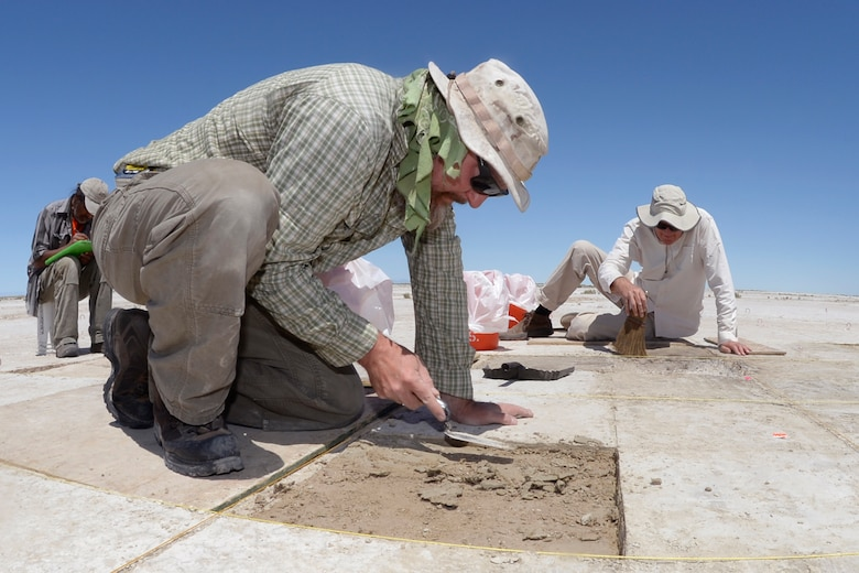 Eric Gingerich, foreground, and Kelly McGuire, both with Far Western Anthropological Research Group, work at a dig site on the Utah Test and Training Range, July 13, 2016. Artifacts found at the site included water fowl bones, seeds, and a large spear tip. (U.S. Air Force photo by Todd Cromar)