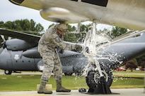 Master Sgt. Matthew Tabor breaks a bottle to christen an H-21B helicopter in Heritage Park at Little Rock Air Force Base, Ark., July 14, 2016. Air Force photo by Senior Airman Harry Brexel