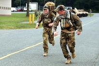 Air Force Staff Sgts. Laura Beckley, left, and Staff Sgt. Samuel Weaver participate in an 8-mile ruck march event during the Fourth Annual Spc. Hilda I. Clayton Best Combat Camera Competition at Fort A.P. Hill, Va., July 12, 2016. Beckley and Weaver are assigned to the 1st Combat Camera Squadron. The ruck march consists of all competitors completing the event with a 35-pound rucksack in a three-hour time limit. Army Photo by Spc. Hayley Gardner