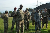 Army Sgt. 1st Class Teddy Wade, foreground, debriefs competitors following an 8-mile ruck march during the Fourth Annual Spc. Hilda I. Clayton Best Combat Camera Competition at Fort A.P. Hill, Va., July 12, 2016. Wade is a platoon sergeant assigned to the 55th Signal Company (Combat Camera). Army photo by Spc. Sara Stalvey