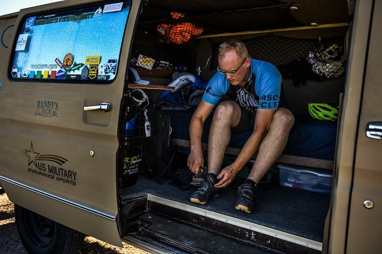 Staff Sgt. Kyle Emmel, a 17th Training Group student, fastens his cycling shoes before a ride in San Angelo, Texas, July 19, 2016. Emmel customized the interior of his van so he could take his bike everywhere he goes. The van is divided into two sections, including a small living area and a trunk used for bike storage. (U.S. Air Force photo/Senior Airman Devin Boyer)