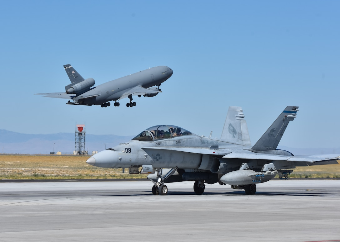 A KC-10 Extender from Travis Air Force Base, California takes off behind an F/A-18 Hornet from Marine Corps Air Station Miramar, California at Mountain Home Air Force Base, Idaho, July 20, 2016. The aircraft participated in multi-national exercise Gunfighter Flag 16-3 held at the Saylor Creek Training Range. (U.S. Air Force photo by Senior Airman Connor J. Marth/RELEASED)