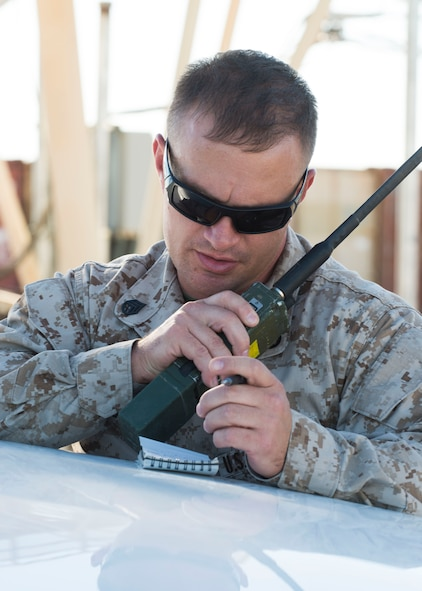 Marine Staff Sgt. Paul Prograis, Joint Terminal Attack Controller evaluator, radios information to his team members at Saylor Creek Range Complex, July 20, 2016. The Marines, visiting from Marine Corps Air Ground Combat Center Twentynine Palms, California, participated in Gunfighter Flag, a multi-national exercise. (U.S. Air Force photo by Senior Airman Malissa Lott/RELEASED)