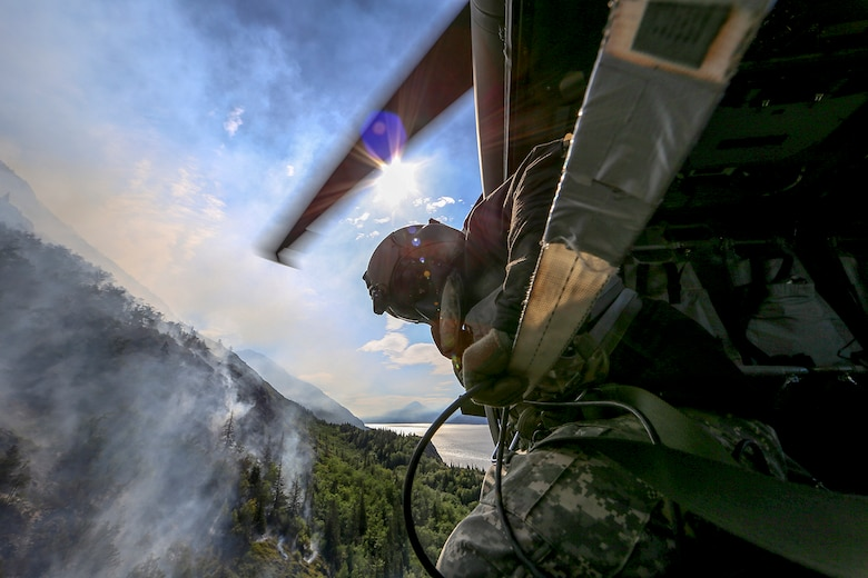 Staff Sgt. Steven Elliot, a crew chief with B Co., 1st Battalion, 207th Aviation Regiment, looks onto the McHugh Creek Fire during operations in support of wildfire suppression efforts near Anchorage, July 20, 2016.