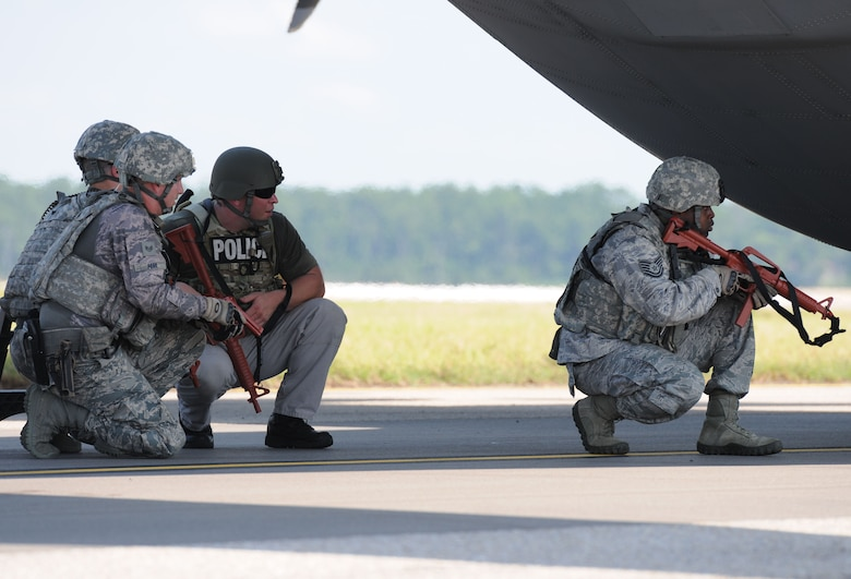 "Members of the 81st Security Forces Squadron approach a WC-130J Super Hercules in attempt to secure the plane after being ""hijacked"" during an anti-hijacking exercise on the flightline July 21, 2016, on Keesler Air Force Base, Miss. The exercise was used to test and maintain the ability of Keesler units to react and respond to developing situations. (U.S. Air Force photo by Kemberly Groue/Released)"