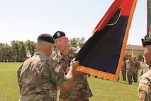 Maj. Gen. Wayne W. Grigsby Jr., 1st Infantry Division and Fort Riley commanding general, passes the brigade colors to Col. David Gardner, commander of 2nd Armored Brigade Combat Team, 1st Inf. Div., July 15 at a change of command and responsibility ceremony. Gardner took command from Col. Miles E. Brown, who led the brigade for two years.