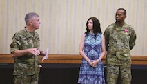 Maj. Gen. Wayne W. Grigsby Jr., 1st Infantry Division and Fort Riley commanding general, left, talks about the contributions of the Cole family before the change of command ceremony July 13 at Riley's Conference Center. Col. Andrew Cole Jr. pictured with his wife Charlotte, was the garrison commander at Fort Riley for three years. Col. John Lawrence took command during the ceremony.