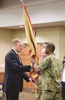 Col. Andrew Cole Jr., outgoing garrison commander, hands the guidon to Joe Capps, Installation Management Command Central Region director, signifying the end of his command at Fort Riley July 13 at Riley's Conference Center.