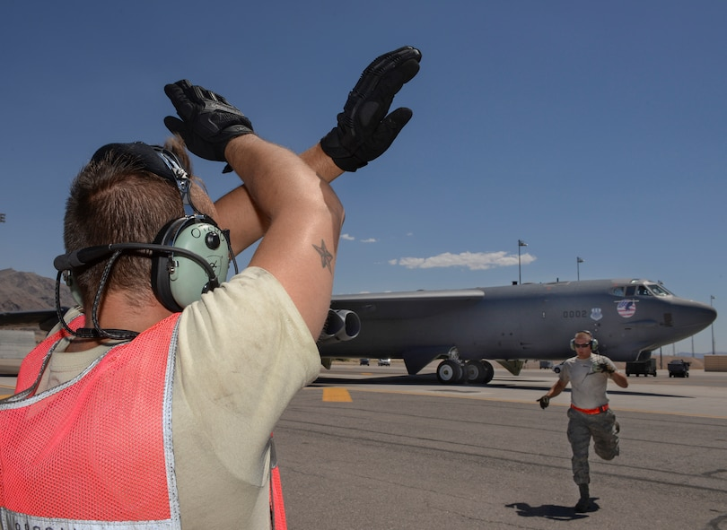Senior Airman Joshua Otero, 96th Bomb Squadron crew chief, Barksdale Air Force Base, La., signals to a B-52 Stratofortress as Senior Airman Elias Sapp, 96th BS crew chief, runs to place before takeoff during Red Flag 16-3 at Nellis Air Force Base, Nev., July 18, 2016. Throughout Red Flag, crew chiefs launch aircraft in day and night operations providing various training scenarios that may differ from their home station. (U.S. Air Force photo by Senior Airman Kristin High/Released)
