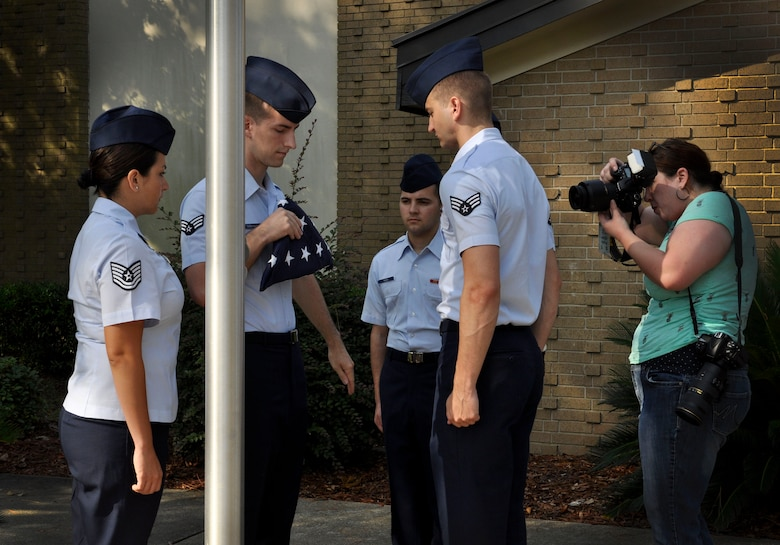 Tech. Sgt. Cassandra Cruz, 81st Force Support Squadron Airman Leadership School instructor, has her photo taken while instructing Airmen on flag folding at the ALS building, July 21, 2016, on Keesler Air Force Base, Miss. Cruz was selected as one of 2015's 12 Outstanding Airmen of the Year. Volunteers assisted in providing staged photos of Cruz on the job for display in the Pentagon. (U.S. Air Force photo by Tech. Sgt. Kimberly Rae Moore/Released)