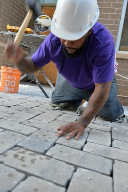 A brick mason pounds a paving brick in to place in the courtyard between the new dormitory buildings here, July 22, 2016, at the I.G. Brown Training and Education Center in Louisville, Tenn. (U.S. Air National Guard photo by Master Sgt. Jerry D. Harlan)