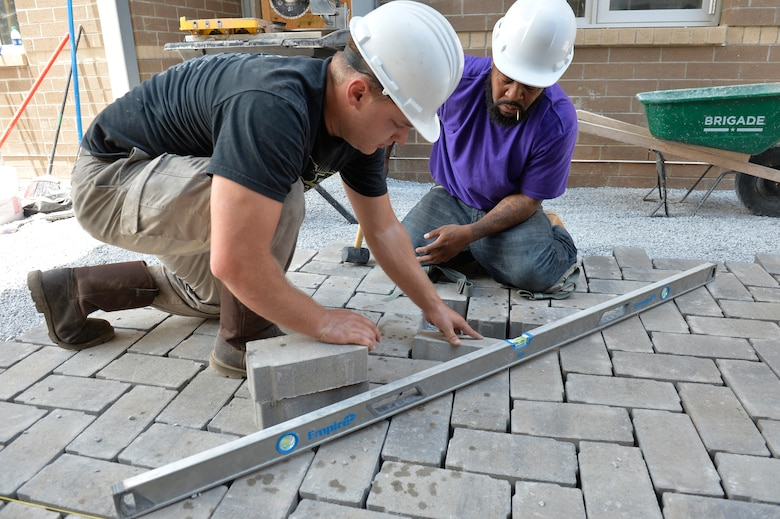 Workers lay and level paving bricks in the courtyard between the new dormitory buildings here, July 22, 2016, at the I.G. Brown Training and Education Center in Louisville, Tenn. (U.S. Air National Guard photo by Master Sgt. Jerry D. Harlan)