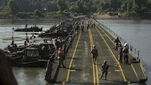 Marines with Bridge Company, 8th Engineer Support Battalion, Bridge Co. Bravo, 6th ESB and U.S. Army soldiers with 814th Multi-Roll Bridge Co. begin allowing vehicles to cross the continuous span bridge during Exercise River Assault on Fort Chaffee, July 19, 2016. The Marines spent two weeks operating Mk3 bridge erection boats and practicing connecting IRBs in preparation for the final exercise, which was a continuous IRB spanned across the Arkansas River.