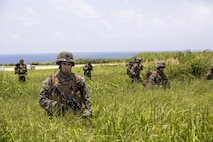 U.S. Marines hike to their designated position to set up security around an air strip July 20, 2016 2016 at Iejima, Okinawa, Japan. Marines immediately set up security, simulated engaging the enemy and set up a combat operations center after getting off an MV-22B Osprey Tiltrotor Aircraft. The Marines were a part of Golf Company, 2nd Marine Division currently attached to 4th Marine Regiment, 3rd Marine Division, III Marine Expeditionary Force through the unit deployment program. (U.S. Marine Corps photo by Lance Cpl. Amaia Unanue/Released)