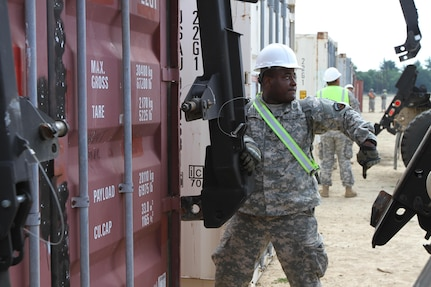 FORT MCCOY,Wisc.-- Spc. Jonathan Bryant, a cargo specialist from Los Angeles with the 211th Inland Cargo Transportation Company, based in Orange County, Calif., prepares to hook a loader to a connex for the Trans Warrior exercise, lasting from July 9 to July 23, 2016. Soldiers of the 211th hone and evaluate their individual and unit collective tasks during Trans Warrior, here (U.S. Army Reserve photo by Spc James C. Blackwell, 206 Broadcast Operations Detachment)