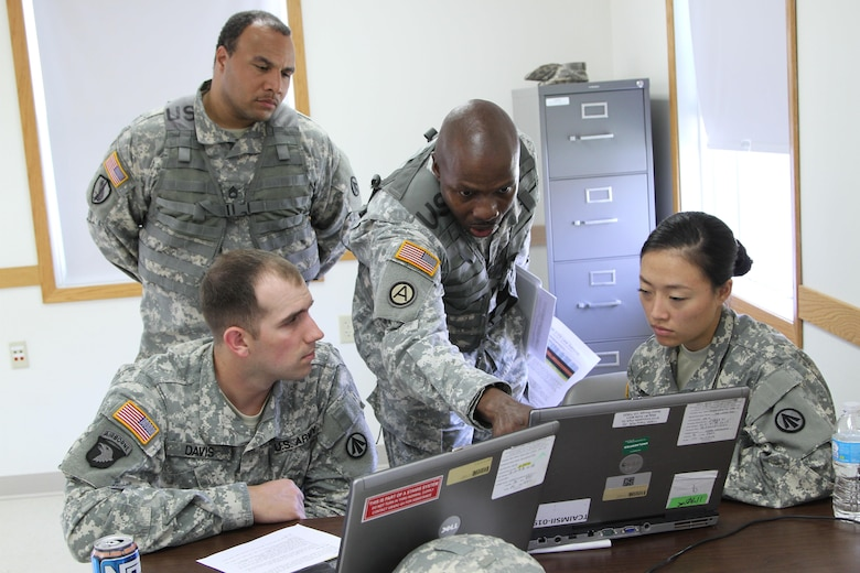 FT. MCCOY, Wisc. – Master Sgt. Duane Emerson, center, and Sgt 1st Class William Thomas, left back, Observer/Controller/Trainers for the Trans Warrior exercise, look over a scenario given in Transportation Coordinators' Automated Information for Movement System II with Sgt. Andrew Davis, far left, and Spc. Jiuen Jun, members of the 931st Expeditionary Theatre Opening Element, based out of Sherman Oaks, Calif.. Trans Warrior was held July 9 through 23, here, providing U.S. Army Reserve transportation Soldiers an opportunity to train realistically on port operations. (U. S. Army Reserve photo by Sgt. Charlotte Fitzgerald, 345th Public Affairs Detachment)