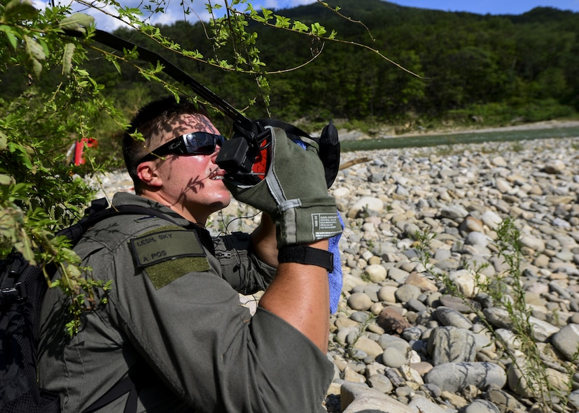 First Lt. Sky Lesh, 25th Fighter Squadron pilot, operates an emergency radio while waiting for an Air Force rescue team to pick him up during Exercise Pacific Thunder 16-2 in the Republic of Korea, July 19, 2016. This two-week long exercise is designed to train and validate tactics, techniques and procedures for combat search and rescue and air suppression of enemy defenses. Lesh acted as a downed pilot for a combat search and rescue training mission, involving rescue personnel deployed here from other Pacific Air Forces units working with Team Osan. This photo has been edited for privacy reasons. (U.S. Air Force photo illustration by Senior Airman Victor J. Caputo/Released)