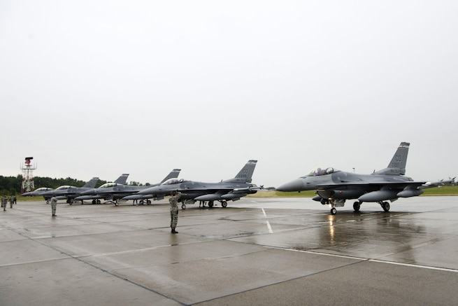 Air Force airmen prepare five F-16 Fighting Falcon aircraft for a rainy-day flight mission at Papa Air Base, Hungary, July 16, 2016. The pilots and crews are assigned to the Colorado Air National Guard's 140th Wing. This is the first time Colorado jets have landed in Hungary. The F-16s will be supporting Operation Atlantic Resolve, and the airmen of the 140th Wing will also be conducting familiarization training alongside Hungary, a NATO ally. Air National Guard photo by Senior Master Sgt. John Rohrer