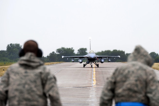 Two Air Force crew chiefs await the first F-16 Fighting Falcon aircraft to land at Papa Air Base, Hungary, as it taxis after landing, July 16, 2016. Air National Guard photo by Senior Master Sgt. John Rohrer