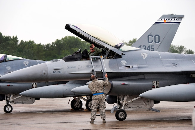 Air Force Master Sgt. John A. Saint George, foreground, sets a ladder for Air Force Capt. James H. Edwards as he prepares to exit his F-16 Fighting Falcon aircraft after landing at Papa Air Base, Hungary, July 16, 2016. Saint George is a crew chief and Edwards is a pilot assigned to the Colorado Air National Guard's 140th Wing. Air National Guard photo by Senior Master Sgt. John Rohrer