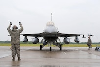 Air Force Master Sgt. John A. Saint George, left, marshals an F-16 Fighting Falcon aircraft into position after landing while a crew chief prepares to chalk the wheels at Papa Air Base, Hungary, July 16, 2016. Saint George is a crew chief and Edwards is a pilot assigned to the Colorado Air National Guard's 140th Wing. Air National Guard photo by Senior Master Sgt. John Rohrer