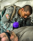 Army Spc. Muhammad Alam checks a simulated casualty's blood pressure during a mass casualty exercise at the Joint Readiness Training Center, Fort Polk, La., July 16, 2016. Alam is assigned to the New York Army National Guard's Headquarters Company, 1st Battalion, 69th Infantry Brigade. Army National Guard photo by Sgt. Harley Jelis
