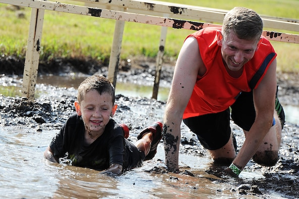 An Airman and his son crawl through the mud during the 2016 Mini Mudder, July 15, 2016 at Minot Air Force Base, N.D. Approximately 900 Airmen and their families attend the event, which lasted 2 hours. (U.S. Air Force photo/Senior Airman Kristoffer Kaubisch)