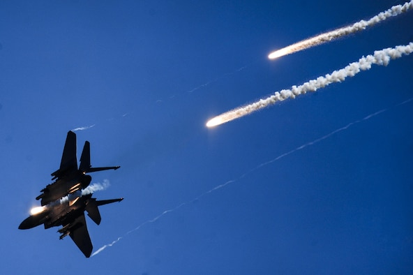 An F-15E Strike Eagle fires multiple flares during a Combined Arms Demonstration as part of the 2015 Wings Over Wayne Air Show, May 17, 2015, at Seymour Johnson Air Force Base, North Carolina. An aerial team of four Strike Eagles and two A-10 Warthogs joined forces to simulate taking over an airfield by eliminating enemy ground forces. (U.S. Air Force photo/Senior Airman Brittain Crolley)