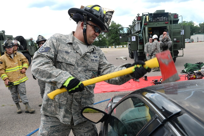 Air Force Staff Sgt. Michael Frye removes a car windshield with an ax during Patriot North 16 at Volk Field, Wis., July 16, 2016. The annual exercise helps the Guard develop working relationships with first responders and government agencies. Air National Guard photo by Senior Master Sgt. David H. Lipp