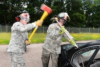 Army Sgt. Somner Goecks, left, swings an ax as Spc. Christopher Schreibner holds a wedge device during vehicle extrication training as part of Patriot North 16 at Volk Field, Wis., July 16, 2016. Goecks and Schreibner are assigned to 826th Ordnance Company. Air National Guard photo by Senior Master Sgt. David H. Lipp