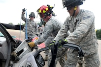 Air Force Staff Sgt. Michael Frye, right, holds a car door while Army Sgt. Somner Goecks operates a hydraulic tool and Air Force Staff Sgt. Joseph Ruppenthal holds hydraulic cables during vehicle extrication training as part of Patriot North 16 at Volk Field, Wis., July 16, 2016. Frye and Ruppenthal are firefighters assigned to the West Virginia Air National Guard's 167th Civil Engineer Squadron. Goecks is a firefighter assigned to the 826th Ordnance Company. Air National Guard photo by Senior Master Sgt. David H. Lipp