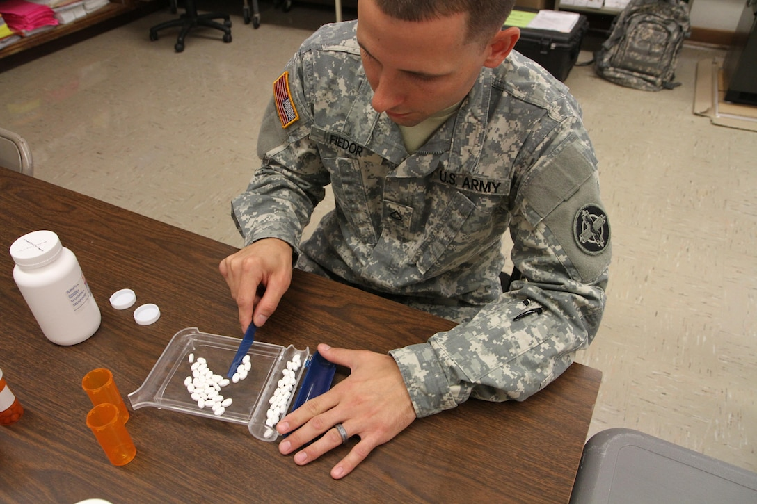 Pfc. Michael Fiedor, a pharmacy technician from Alpha Company, 48th Combat Support Hospital out of Fort Meade, Md., counts pills to fill a prescription during the Greater Chenango Cares Innovative Readiness Training event, July 20, 2016.  Greater Chenango Cares is one of the IRT events that provides real-world training in a joint civil-military environment while delivering world-class medical care to the people of Chenango County, N.Y., from July 15-24.