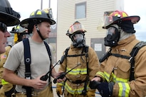 Air Force Tech. Sgt. Samuel Deveral, Staff Sgt. Joshua England and Staff Sgt. Adam King discuss structural live-fire training procedures before entering a burning facility as part of Patriot North 16 at Volk Field, Wis., July 17, 2016. Deveral is a firefighter assigned to the West Virginia Air National Guard's 167th Civil Engineer Squadron. England and King are firefighters assigned to the Illinois Air National Guard's 182nd Civil Engineer Squadron. Patriot North 2016 is an annual exercise to test the National Guard's capabilities and develop working relationships with first responders and government agencies. Air National Guard photo by Senior Master Sgt. David H. Lipp