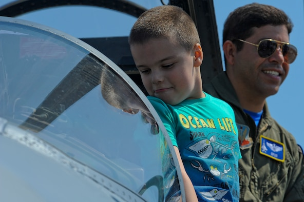 Matei Codobam, 7, looks inside the cockpit of Massaschusetts Air National Guard F-15C Eagle fighter aircraft assigned to the 104th Fighter Wing, Barnes ANG Base, Mass., while California ANG Lt. Col. Paul Shamy, a 194th Expeditionary Fighter Squadron F-15C pilot, waits to pose for a photo taken by Matei's family during the Romanian air force's 71st Air Base's air show and open house at Campia Turzii, Romania, July 23, 2016. The aviation demonstration took place during the middle of the U.S. Air Force's 194th Expeditionary Fighter Squadron's six-month long theater security package deployment to Europe in support of Operation Atlantic Resolve, which aims to bolster the U.S.'s continued commitment to the collective security of NATO and dedication to the enduring peace and stability in the region. The unit, comprised of more than 200 CANG Airmen from the 144th Fighter Wing at Fresno ANG Base, Calif., as well as U.S. Air Force Airmen from the 52nd Fighter Wing at Spangdahlem Air Base, Germany, piloted, maintained and supported the deployment of 12 F-15Cs Eagle fighter aircraft throughout nations like Romania, Iceland, the United Kingdom, the Netherlands, Estonia and among others. The F-15Cs took to the skies alongside the 71st AB's MiG-21 fighter aircraft and Puma helicopters for both the airshow, the second engagement of its kind at Campia Turzii under Operation Atlantic Resolve, and the bilateral flight training, also known as Dacian Eagle 2016. The 194th EFS partnered with the 104th EFS's previous deployment as part of the theater security package, including a contingent of 104th FW aircraft which remained at Campia Turzii. (U.S. Air Force photo by Staff Sgt. Joe W. McFadden/Released)