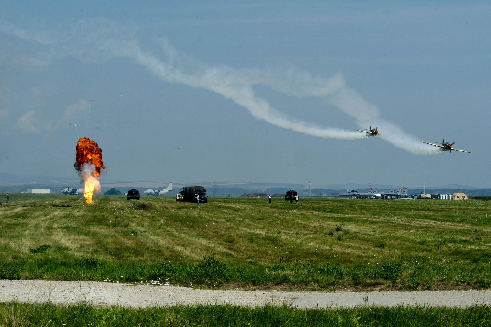 Two specialized Yakovlev Yak-52 trainer aircraft participate in a simulated bombing drill during the Romanian air force's 71st Air Base's air show and open house at Campia Turzii, Romania, July 23, 2016. The aviation demonstration took place during the middle of the U.S. Air Force's 194th Expeditionary Fighter Squadron's six-month long theater security package deployment to Europe in support of Operation Atlantic Resolve, which aims to bolster the U.S.'s continued commitment to the collective security of NATO and dedication to the enduring peace and stability in the region. The unit, comprised of more than 200 CANG Airmen from the 144th Fighter Wing at Fresno ANG Base, Calif., as well as U.S. Air Force Airmen from the 52nd Fighter Wing at Spangdahlem Air Base, Germany, piloted, maintained and supported the deployment of 12 F-15Cs Eagle fighter aircraft throughout nations like Romania, Iceland, the United Kingdom, the Netherlands, Estonia and among others. The F-15Cs took to the skies alongside the 71st AB's MiG-21 fighter aircraft and Puma helicopters for both the airshow, the second engagement of its kind at Campia Turzii under Operation Atlantic Resolve, and the bilateral flight training, also known as Dacian Eagle 2016. (U.S. Air Force photo by Staff Sgt. Joe W. McFadden/Released)