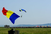 A parachutist floats to the ground while bearing a large Romanian flag before hundreds of spectators during the Romanian air force's 71st Air Base's air show and open house at Campia Turzii, Romania, July 23, 2016. The aviation demonstration took place during the middle of the U.S. Air Force's 194th Expeditionary Fighter Squadron's six-month long theater security package deployment to Europe in support of Operation Atlantic Resolve, which aims to bolster the U.S.'s continued commitment to the collective security of NATO and dedication to the enduring peace and stability in the region. The unit, comprised of more than 200 CANG Airmen from the 144th Fighter Wing at Fresno ANG Base, Calif., as well as U.S. Air Force Airmen from the 52nd Fighter Wing at Spangdahlem Air Base, Germany, piloted, maintained and supported the deployment of 12 F-15Cs Eagle fighter aircraft throughout nations like Romania, Iceland, the United Kingdom, the Netherlands, Estonia and among others. The F-15Cs took to the skies alongside the 71st AB's MiG-21 fighter aircraft and Puma helicopters for both the airshow, the second engagement of its kind at Campia Turzii under Operation Atlantic Resolve, and the bilateral flight training, also known as Dacian Eagle 2016. (U.S. Air Force photo by Staff Sgt. Joe W. McFadden/Released)
