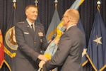 Air Force Lt. Gen. Andy Busch, DLA director, hands the organization colors to Air Force Brig. Gen. Martin Chapin, incoming DLA Energy commander, in a ceremony at Fort Belvoir, Virginia, July 22.