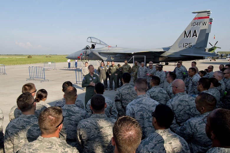 California Air National Guard Maj. Gen. Jon Kelk, both the ANG mobilization assistant to the U.S. Air Forces in Europe/Air Forces Africa commander and the commander, chief of staff of the CANG,  speaks to Airmen assigned to the 194th Expeditionary Fighter Squadron in front of a Massaschusetts Air National Guard F-15C Eagle fighter aircraft assigned to the 104th Fighter Wing, Barnes ANG Base, Mass., during the Romanian air force's 71st Air Base's air show and open house at Campia Turzii, Romania, July 23, 2016. The aviation demonstration took place during the middle of the 194th EFS' six-month long theater security package deployment to Europe in support of Operation Atlantic Resolve, which aims to bolster the U.S.'s continued commitment to the collective security of NATO and dedication to the enduring peace and stability in the region. The unit, comprised of more than 200 CANG Airmen from the 144th Fighter Wing at Fresno ANG Base, Calif., as well as U.S. Air Force Airmen from the 52nd Fighter Wing at Spangdahlem Air Base, Germany, piloted, maintained and supported the deployment of 12 F-15Cs Eagle fighter aircraft throughout nations like Romania, Iceland, the United Kingdom, the Netherlands, Estonia and among others. The F-15Cs took to the skies alongside the 71st AB's MiG-21 fighter aircraft and Puma helicopters for both the airshow, the second engagement of its kind at Campia Turzii under Operation Atlantic Resolve, and the bilateral flight training, also known as Dacian Eagle 2016. The 194th EFS partnered with the 104th EFS's previous deployment as part of the theater security package, including a contingent of 104th FW aircraft which remained at Campia Turzii. (U.S. Air Force photo by Staff Sgt. Joe W. McFadden/Released)