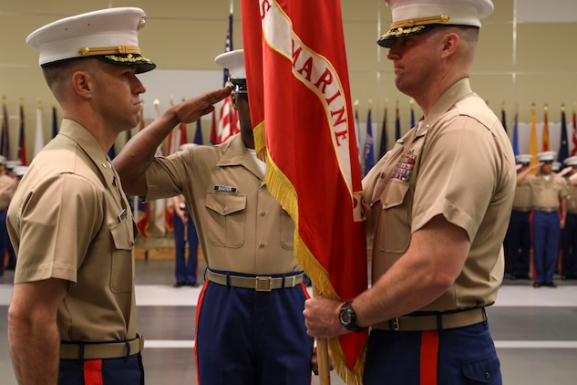 U.S. Marine Corps Maj. Paul B. Bock, right, prepares to give the organizational colors to U.S. Marine Corps Maj. Luke A. Sauber during Recruiting Station Frederick's change of command ceremony June 28, 2016 at Fort Detrick. The passing of the colors signifies a formal transfer of authority and responsibility from one commanding officer to another. Bock is the outgoing commanding officer of the recruiting station, while Sauber is the incoming commanding officer.