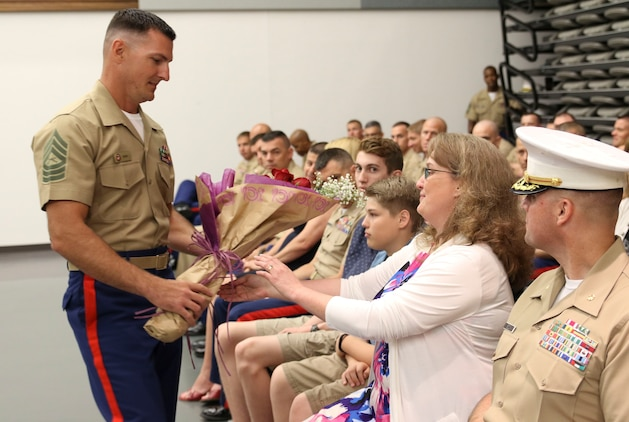 Jennifer Bock receives flowers from Marine Corps Master Sgt. Michael Nash during Recruiting Station Frederick's change of command ceremony June 28, 2016 at Fort Detrick. The flowers were in recognition of her support, dedication and devotion to her husband's assignment as Recruiting Station Frederick's commanding officer. Nash is a recruiter instructor with the station.
